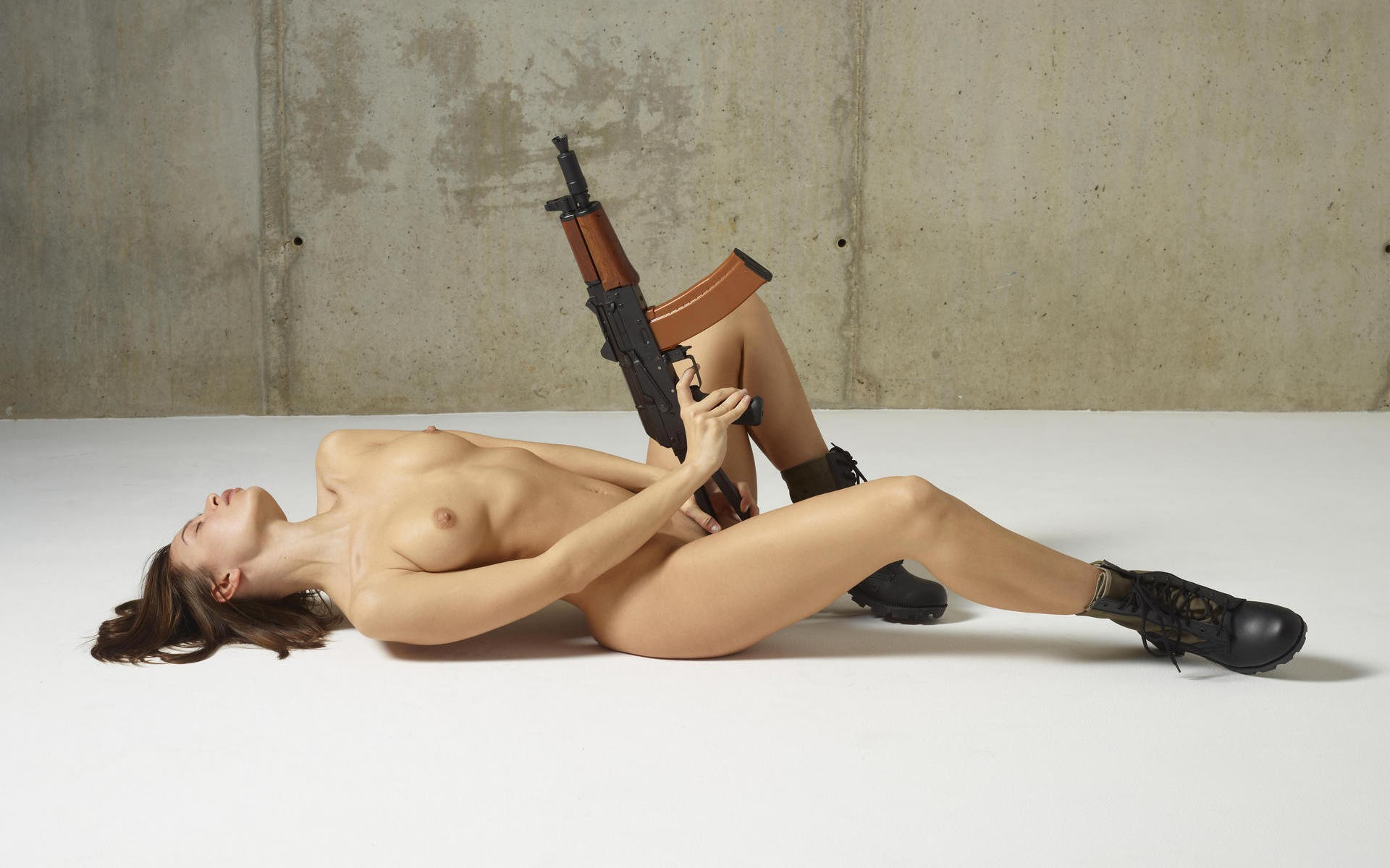 Russian solo girl poses naked with guns and knives in a wine colored beret